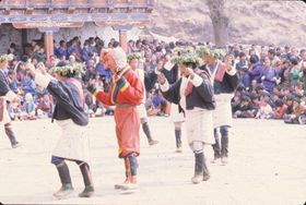 Laymen from the Uchu village in Paro with their characteristic foliage headdress, and an atsara: They perform the dance of Uchu (U chu gzhas), Paro Tshechu (tshe bcu), afternoon, 5th day