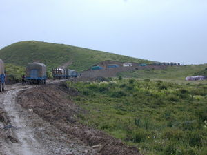 Trucks climbing dirt road and crossing pass.