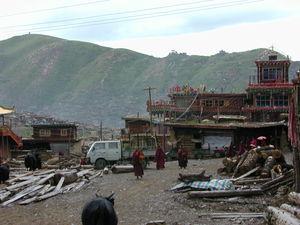 Monks walking near the main Assembly Hall ['du khang] of Larung Gar [bla rung gar] religious settlement.