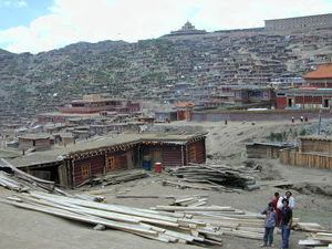 Panorama view of the center of the Larung Gar [bla rung gar] religious settlement with the Gyutrul Temple [sgyu 'phrul lha khang] (left) and Visitors Hostel (right) atop the ridge in back. (Larung Gar, China)