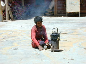 A nomad boiling water in the courtyard of the residence of Khenpo Jigme Phuntsok, the founder of Larung Gar.