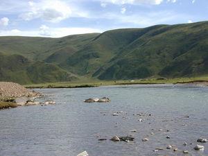 A nomad encampment near a river.
