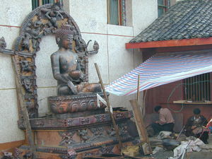 Men working on a Buddha statue.