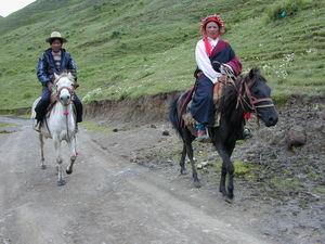 A couple traveling on horseback.