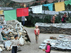 Pilgrims at the pile of prayer flags and prayer stones.