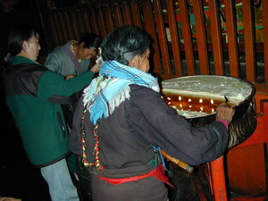 Tibetan women offering butter in butter lamps on the first floor of the temple.