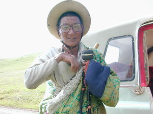 An elderly nomad with prayer wheel and rosary.