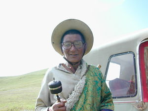 An elderly nomad spinning his prayer wheel.