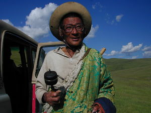 An elderly nomad spinning his prayer wheel and counting his rosary.
