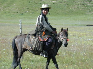 A nomad woman travelling on horseback.