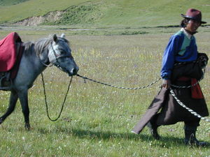 A nomad man leading a horse.