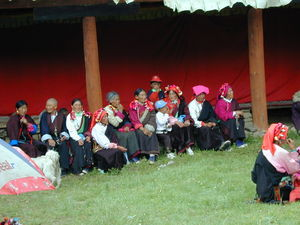 A nomad family seated along the edge of the courtyard waiting for the dances to begin.