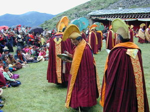 A line of monks wearing yellow hats processing around the courtyard.