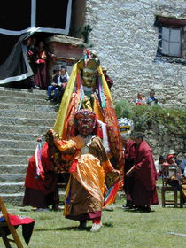 A smaller masked dancer (foreground) and a dancer dressed as Padmasambhava (background) in the courtyard.