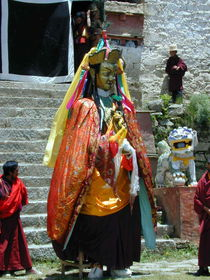 A dancer dressed as Padmasambhava in the courtyard.