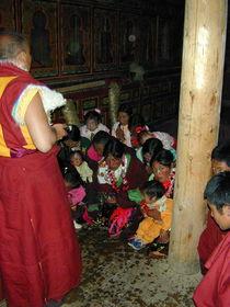 Nomad women and children prostrating before Abbot Dorji Tashi.