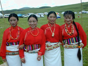 Four dancers wearing red shirts.