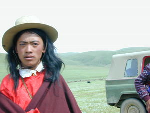 A close up of a long haired young Tibetan man.