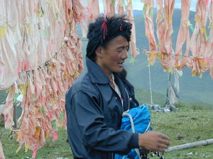 A long-haired nomad man at the prayer flag frame.