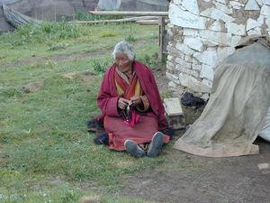 An elderly nun praying with her rosary. (Larung Gar, China)