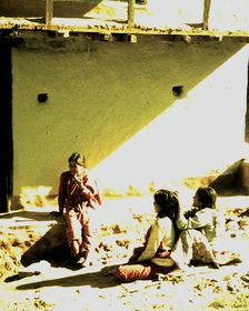 Village women grooming each other in courtyard