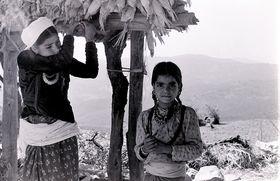 Two village girls near maize storage platform (tengro)