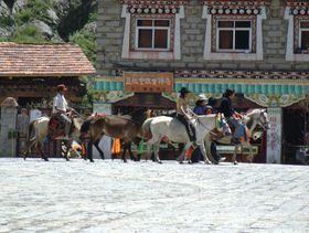 Nomads riding horses in Lhagang town.