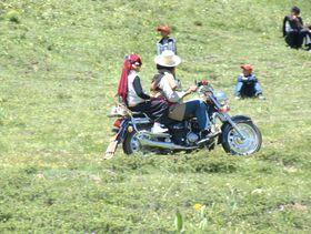 Tibetan nomad couple riding motorcycle.