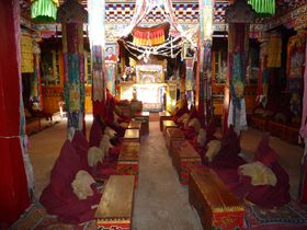 Monks gathered in the assembly hall (<em>'du khang</em>) of Lo Monastery.