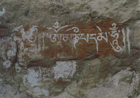 An ancient <i>maṇi mantra</i> in red ochre and a white pigment.