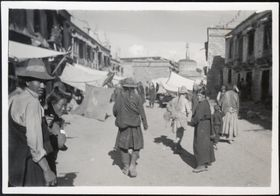 Street in Lhasa's Barkor with people and shops, and a stupa. Copyright Pitt Rivers Museum, University of Oxford 2001.35.161.1